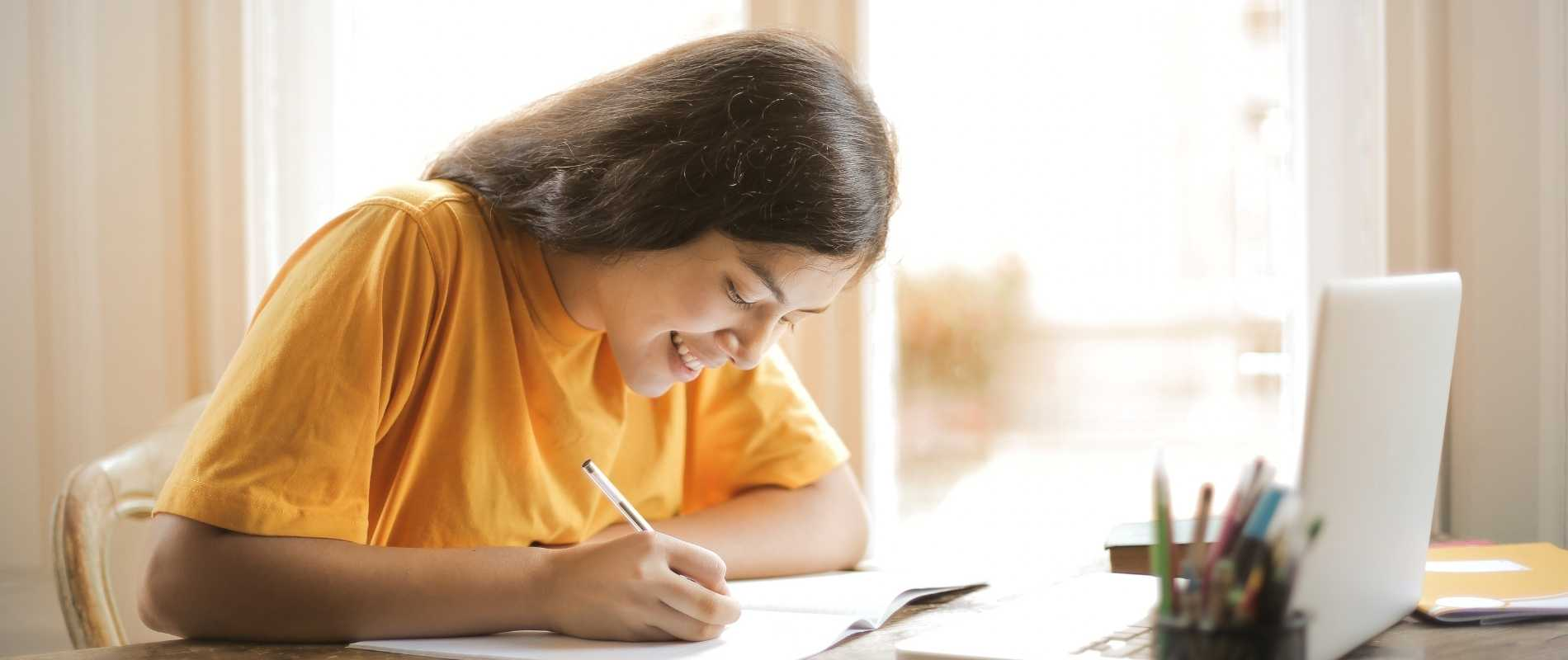 female student writing at desk