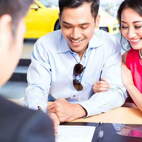 Man and woman looking at lease agreement for car
