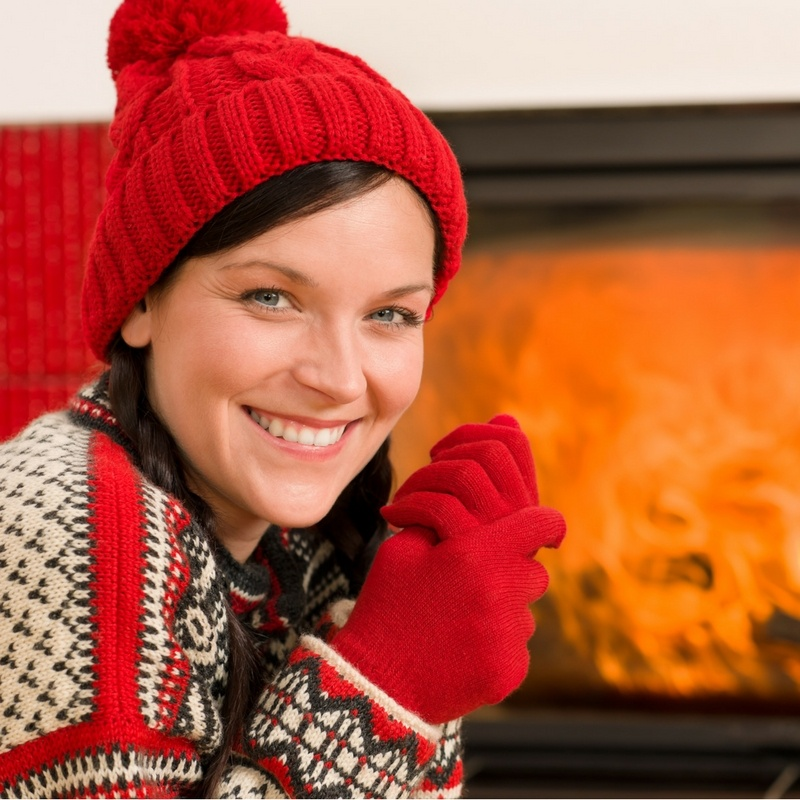 woman wearing hat, gloves, and sweater in front of fireplace