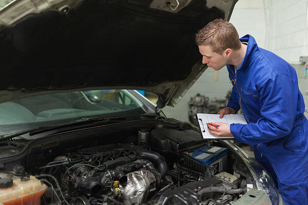 Male mechanic writing on clipboard while examining car engine