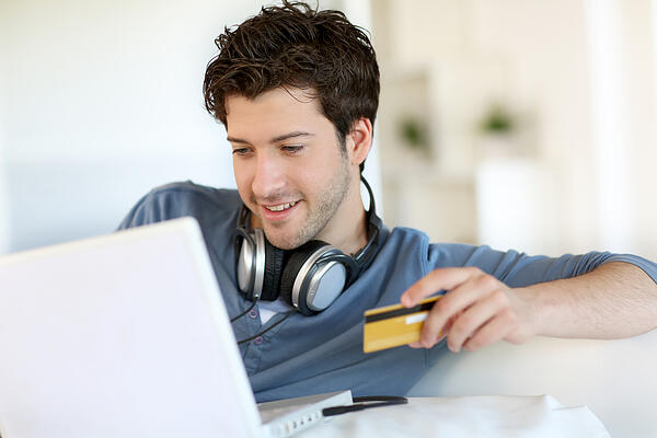 Teenage boy buying music online as authorized user