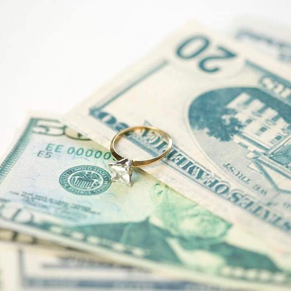 engagement ring on money