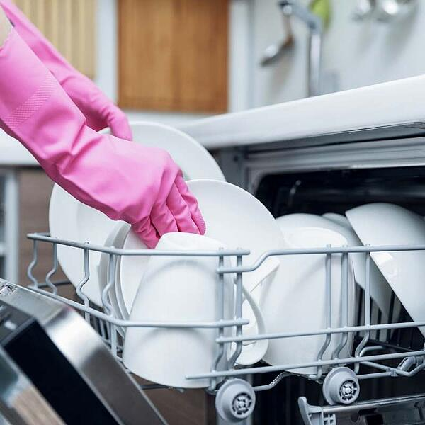 woman using dishwasher to save energy in winter