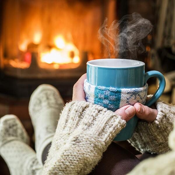 woman drinking from mug in front of fireplace
