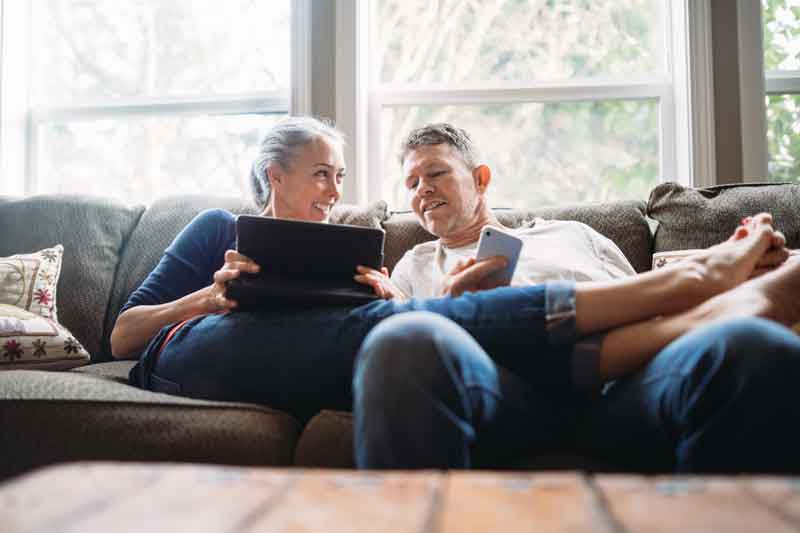couple lounging on couch with laptop and cellphone