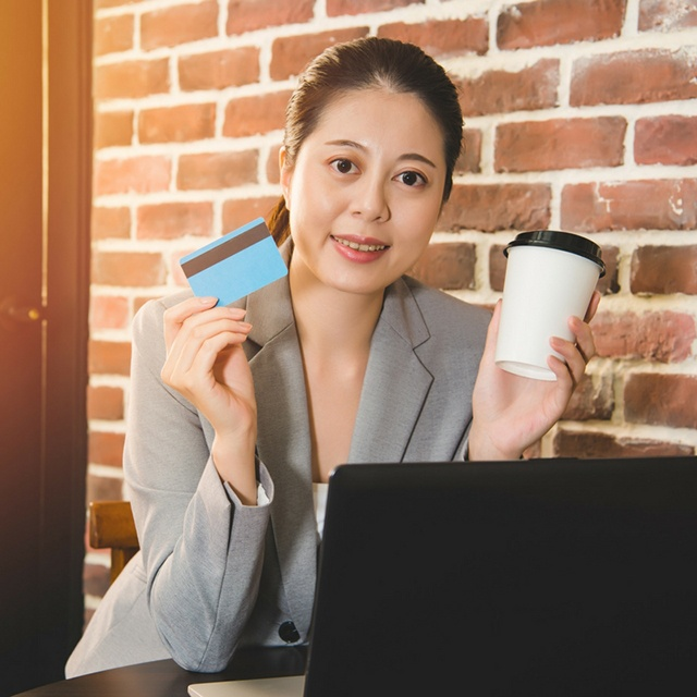 Woman holding a coffee cup and her corporate card