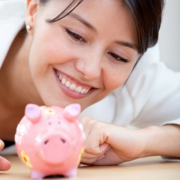 Woman smiling at a piggy bank.jpg