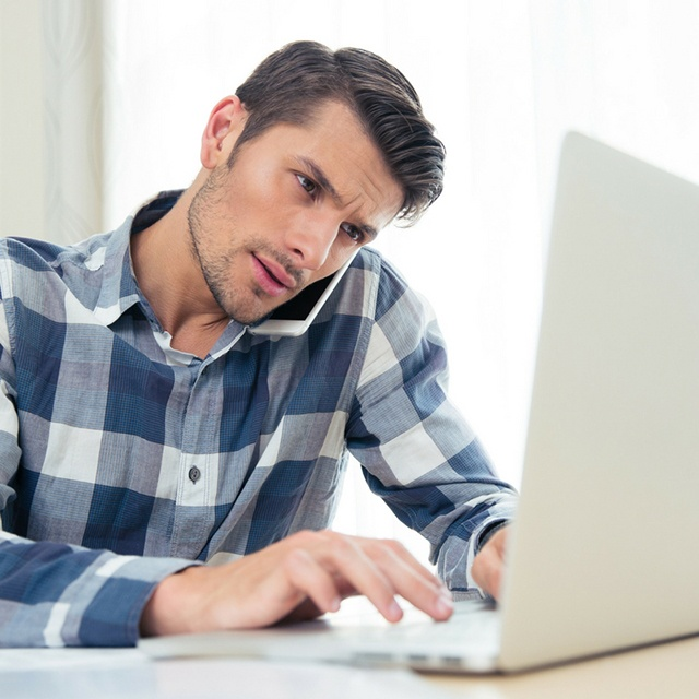 Young man on phone at lap top.jpg
