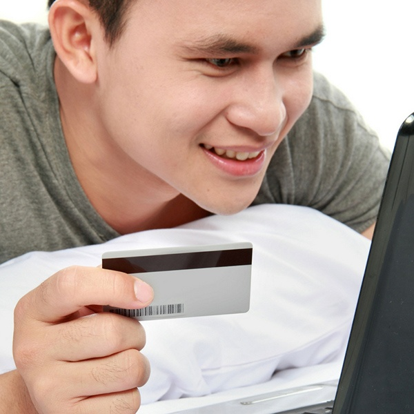 Young man purchasing items on his lap top.jpg