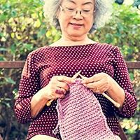 Senior citizen knitting on a park bench.jpg