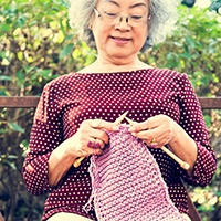Senior citizen knitting on a park bench.jpg
