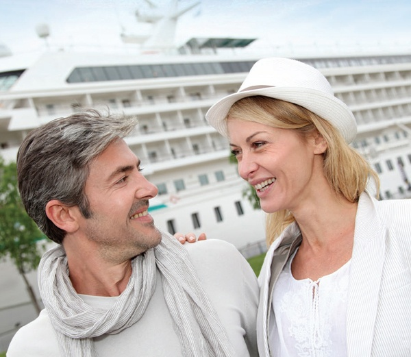 Couple smiling in front of cruise