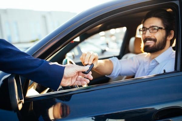 man in new car getting keys