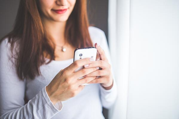woman holding cell phone in her hands