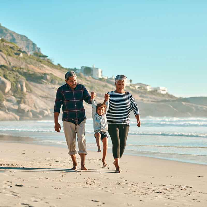 older-couple-on-beach-with-grandchild_webopt