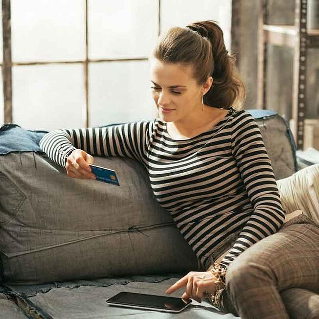 Woman sitting on couch with credit card