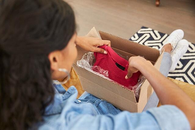 woman opening a box containing a red sweater