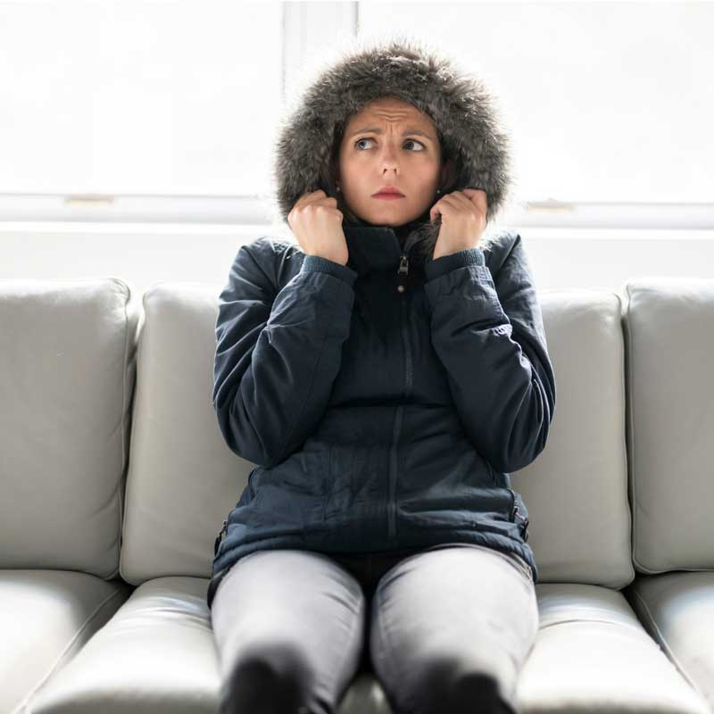woman freezing on couch in winter