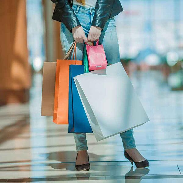 woman standing with shopping bags at mall