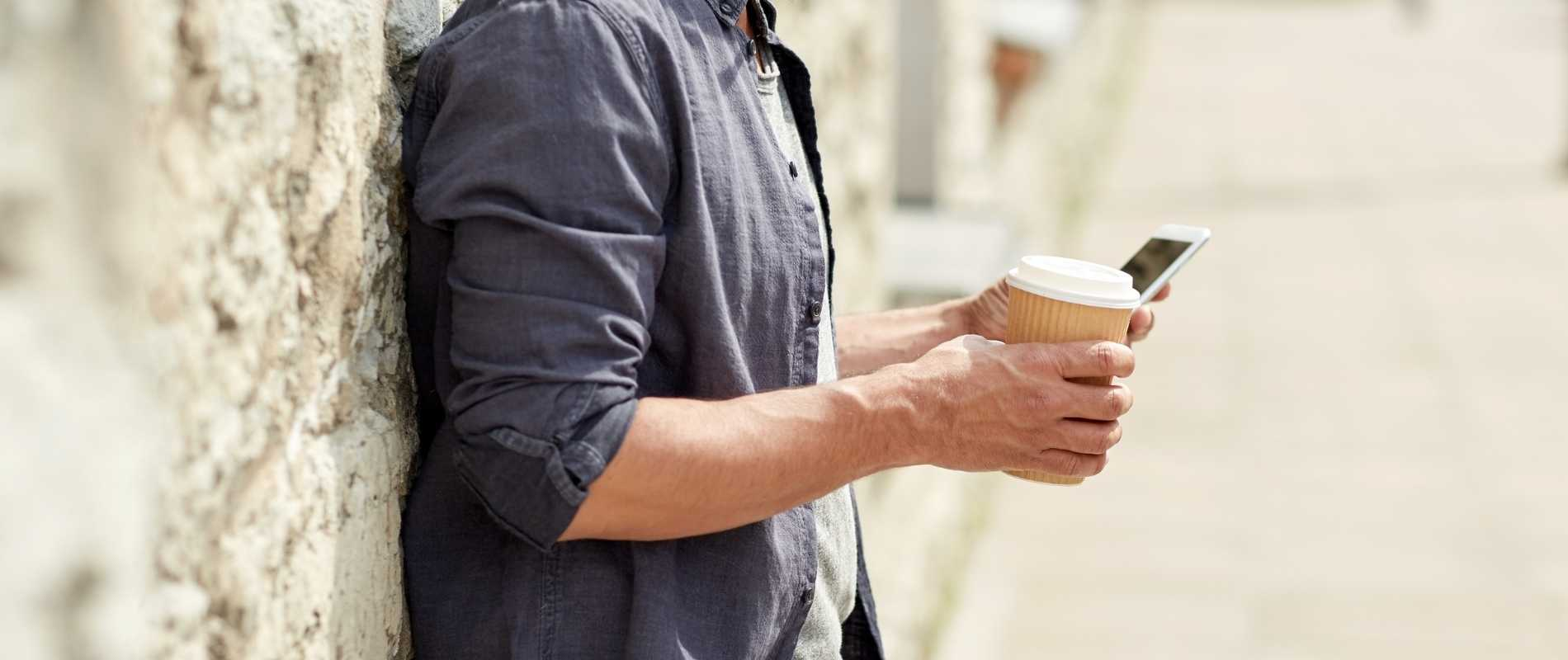 young man leaning against wall with smartphone and coffee in hand