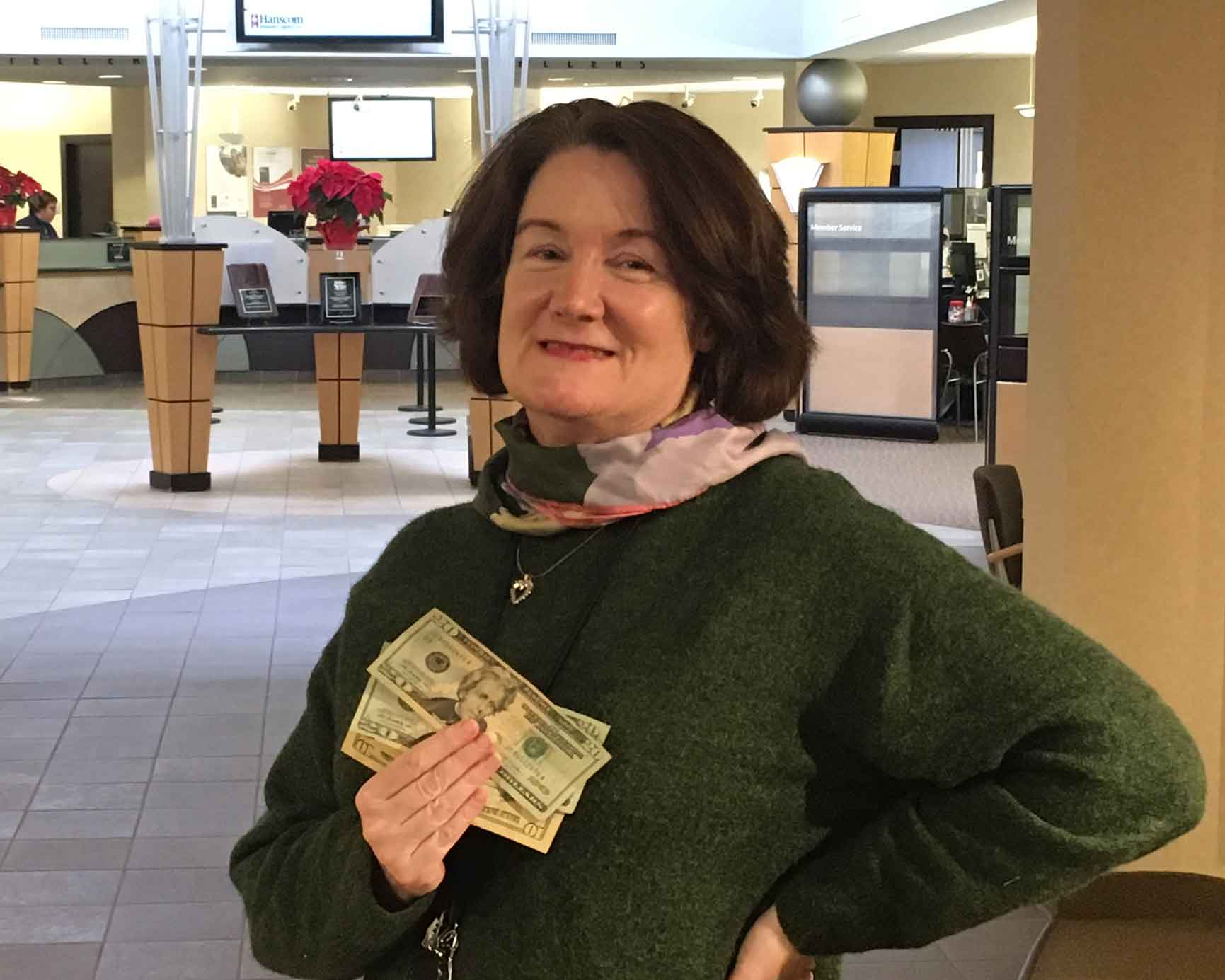 woman holding cash in credit union