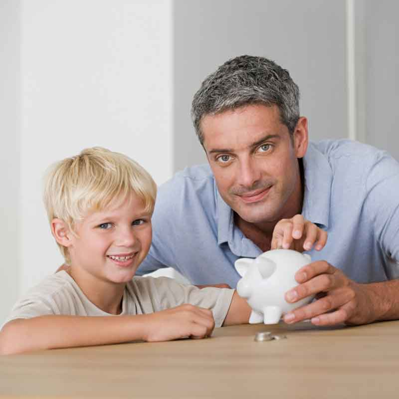 Father and son holding white piggy bank