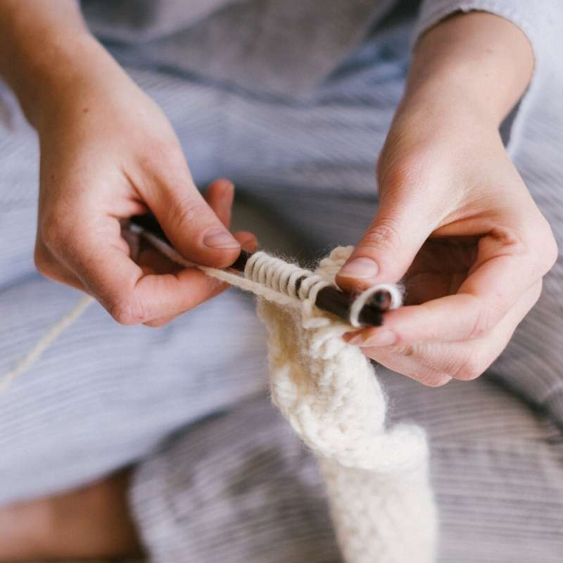 woman knitting while saving money