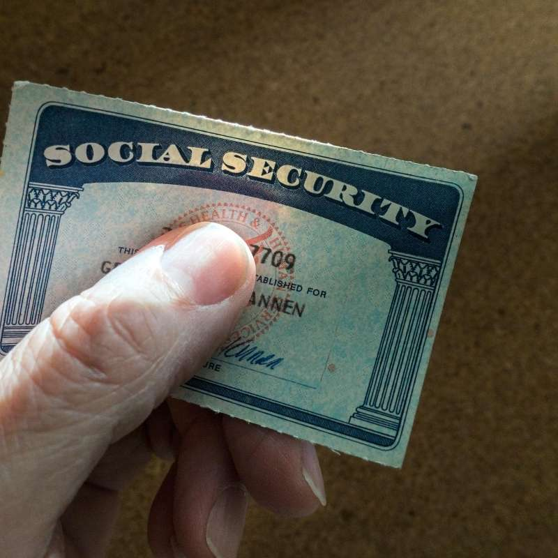 male hand holding social security card
