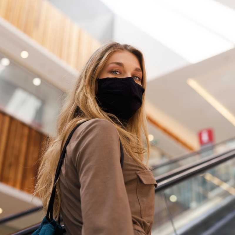 woman on escalator shopping Black Friday during COVID pandemic