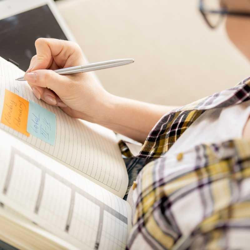 woman writing 2021 smart goals in notebook