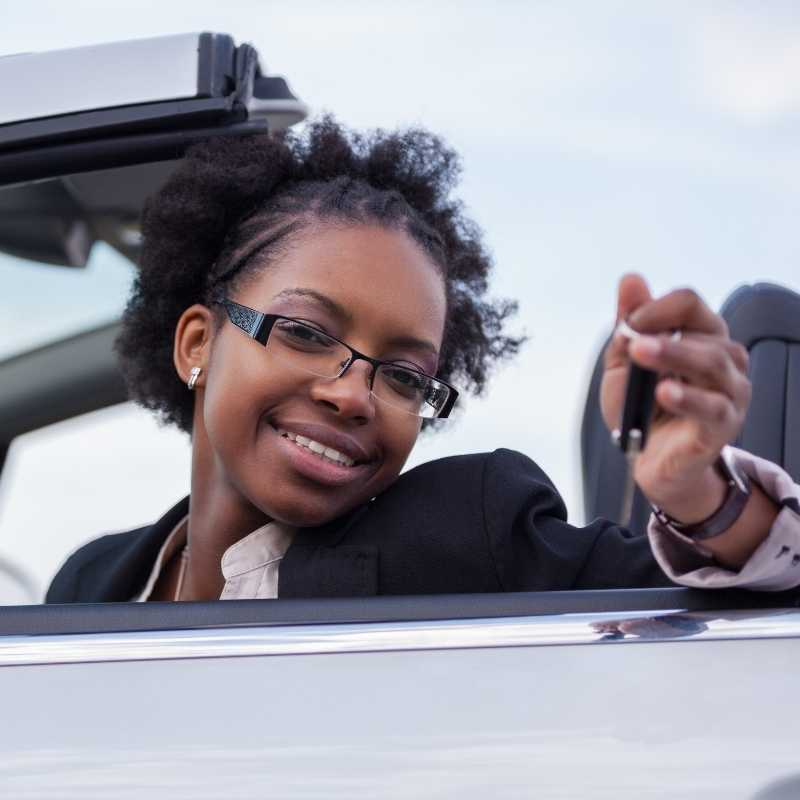 young woman holding key for first car