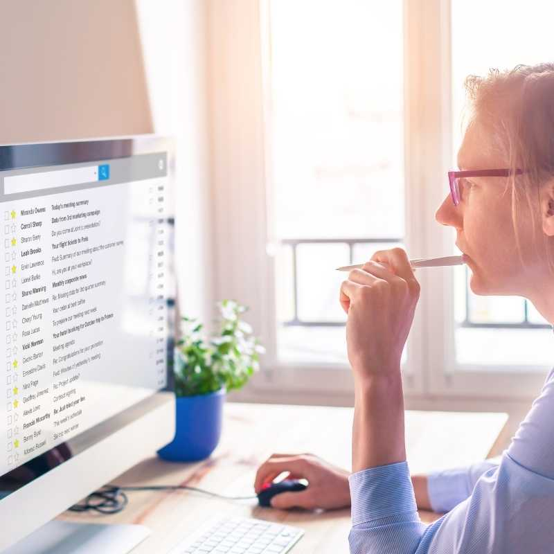 woman reading subscription scam email on computer
