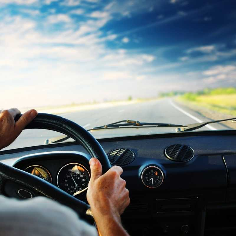 man driving a car on open road