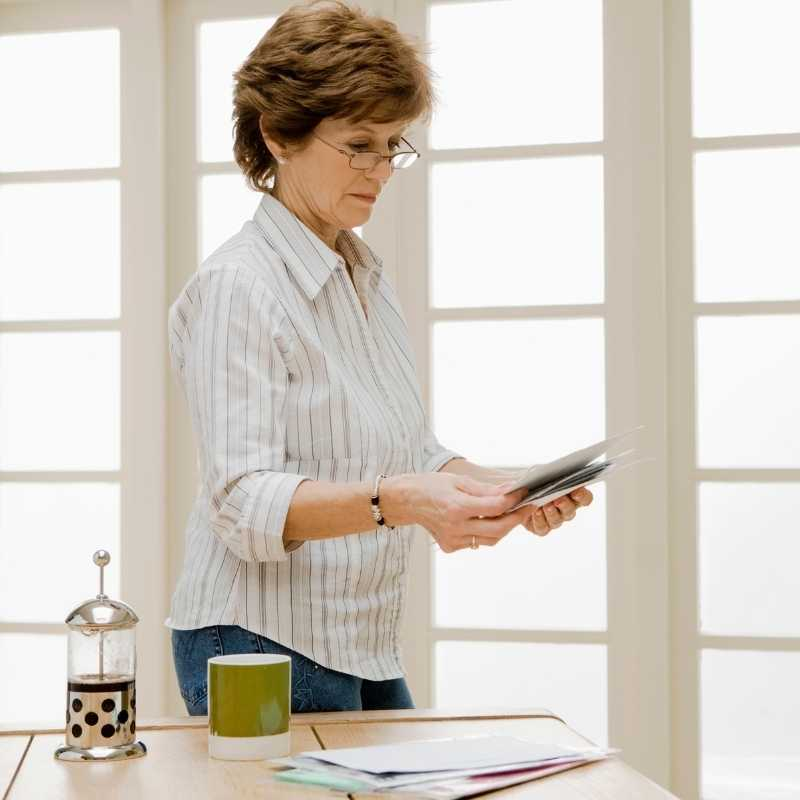 older woman looking at credit card statement with cut credit limit