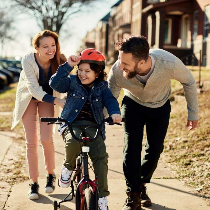 couple helping child ride bike while saving money automatically