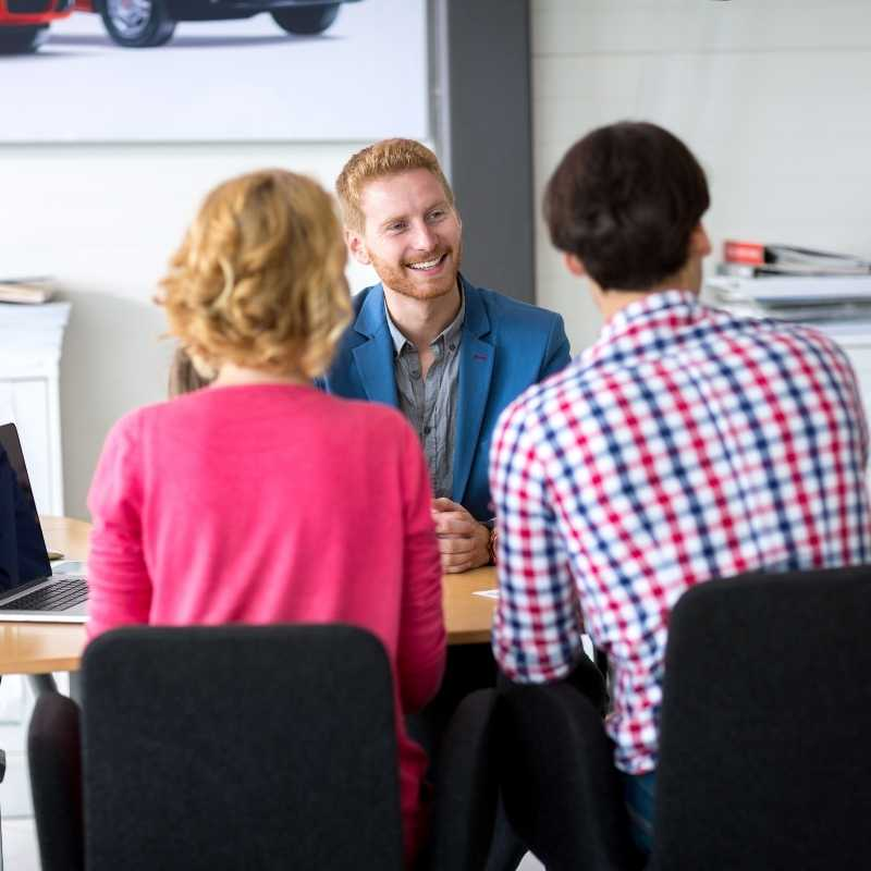 couple negotiating car lease at dealership