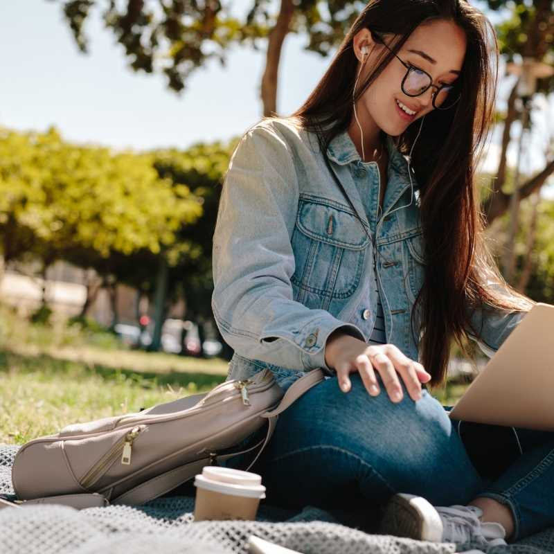 college student outside looking at laptop