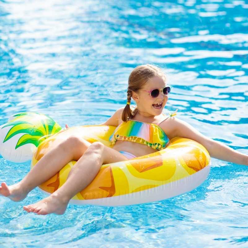 young girl floating in ring in pool during summer