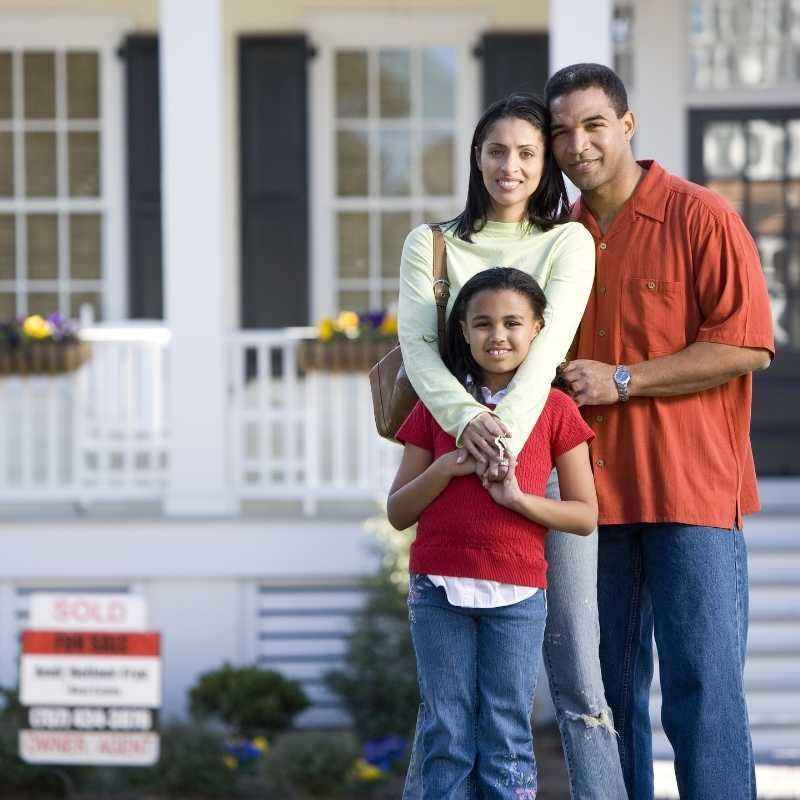 family standing in front of house they bought in bidding war