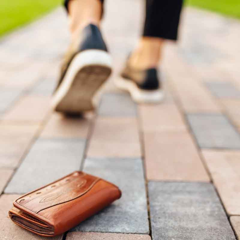 woman walking away from lost wallet